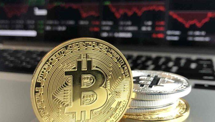 Pildil on aktsiagraafikud arvutiekraanil ning bitcoini münt, mis illustreerib teemat Viini börsil saab osta krüptot nagu aktsiaid