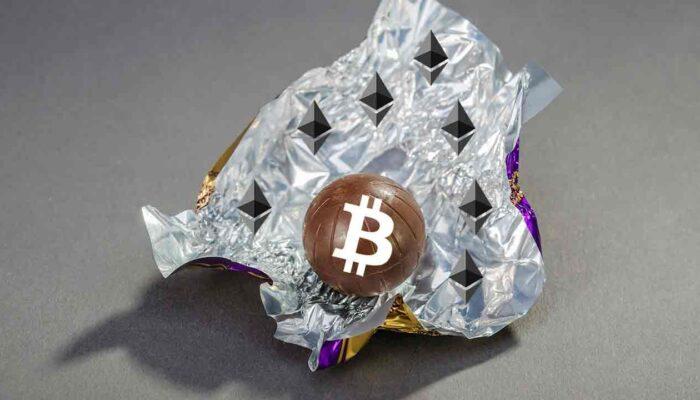 """Pildil on lahtise kommipaberi sees olev """"bitcoini komm"""", mis illustreerib teemat Bitcoinid Ethereumi plokiahelal"""