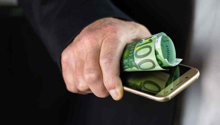 Pildil on käes hoitav nutitelefon ja 100-eurone, mis illustreerib teemat Eesti Pank uurib digiraha tehnoloogiat