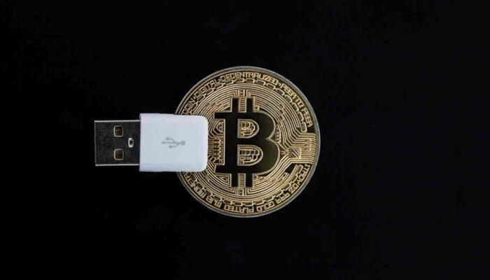 Pildil on Bitcoini münt koos usb-liidesega, mis illustreerib teemat Bitcoin saab 2 tarkvarauuendust